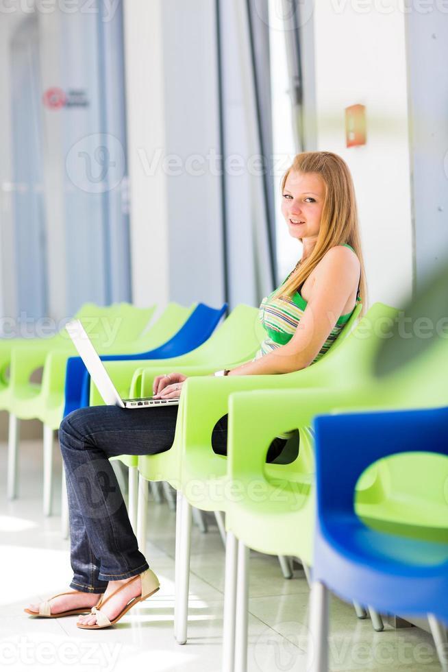vacker, kvinnlig högskolestudent som arbetar på sin bärbara dator foto