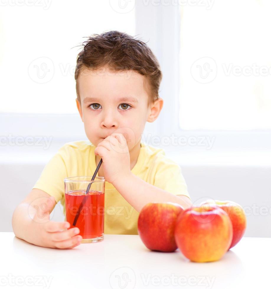 liten pojke med ett glas äppeljuice foto