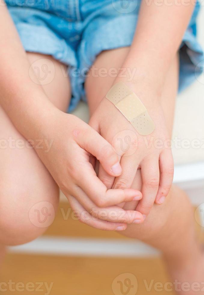 barnhand med ett självhäftande bandage. foto