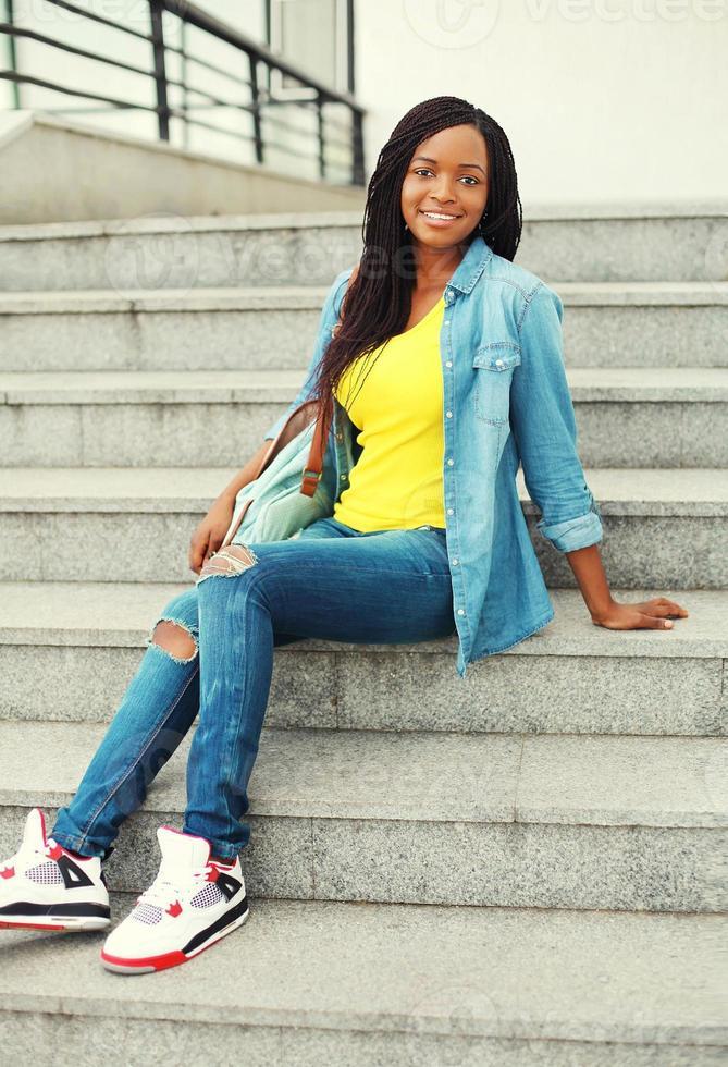vacker glad leende afrikansk kvinna som bär en jeansskjorta och foto