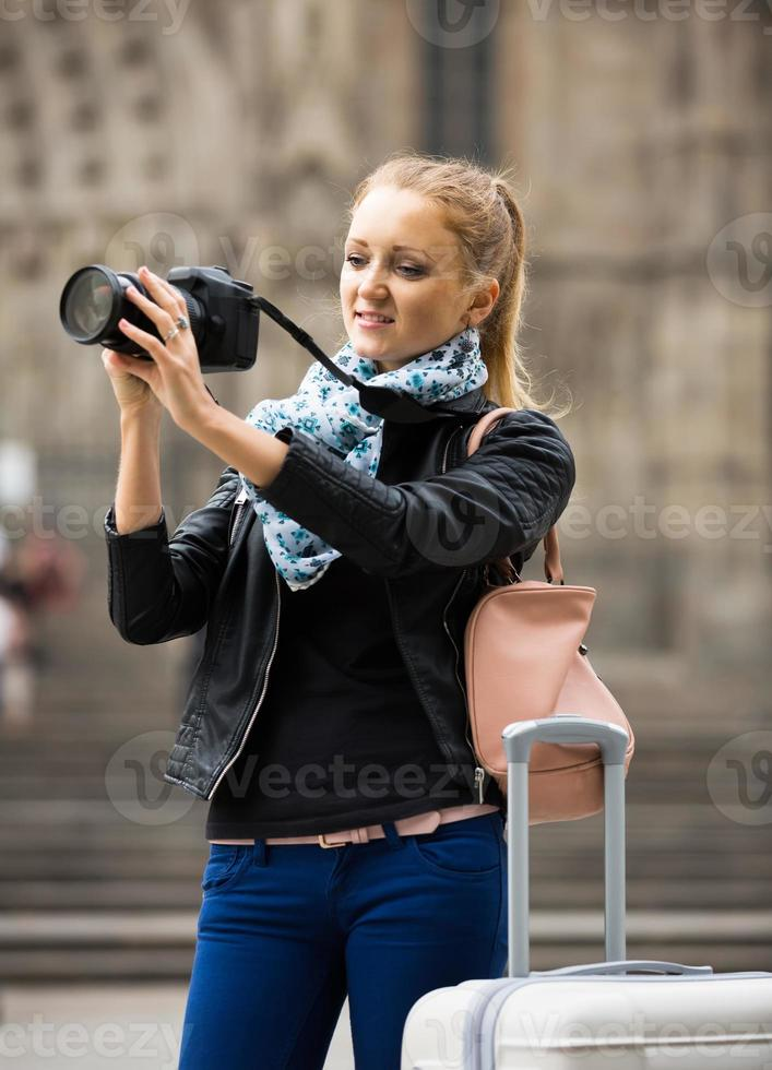 kvinna som går i höststad med digital kamera foto