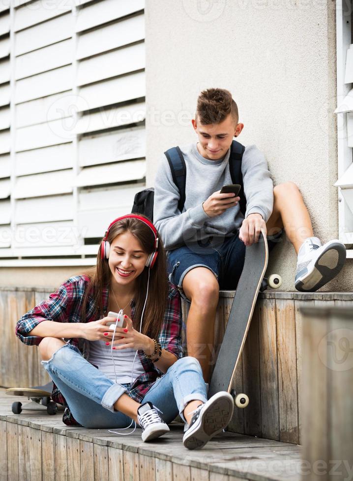 tonåring och hans flickvän med smartphones foto