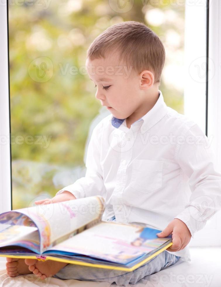 lilla pojken läser bok foto