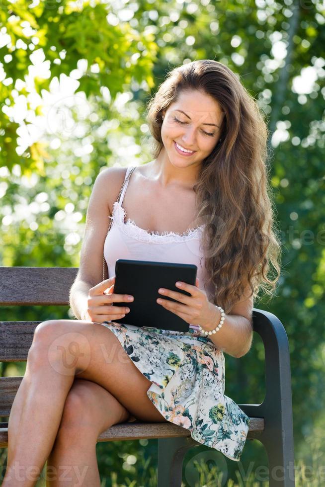 flicka sitter på bänken med ereader foto