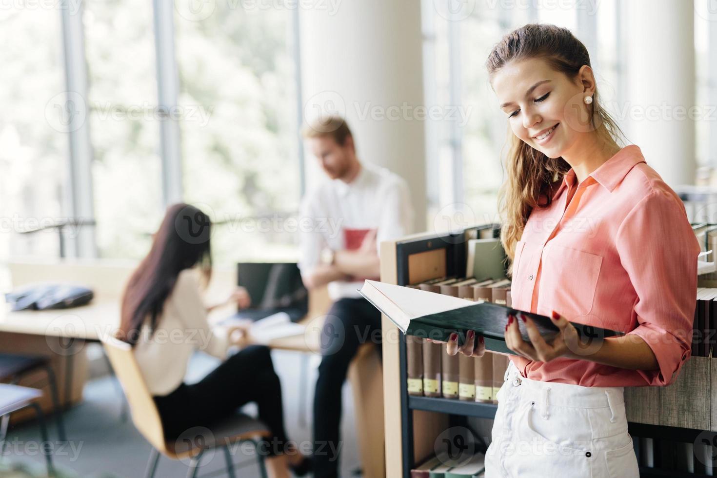 vacker kvinna som läser en bok i ett bibliotek foto