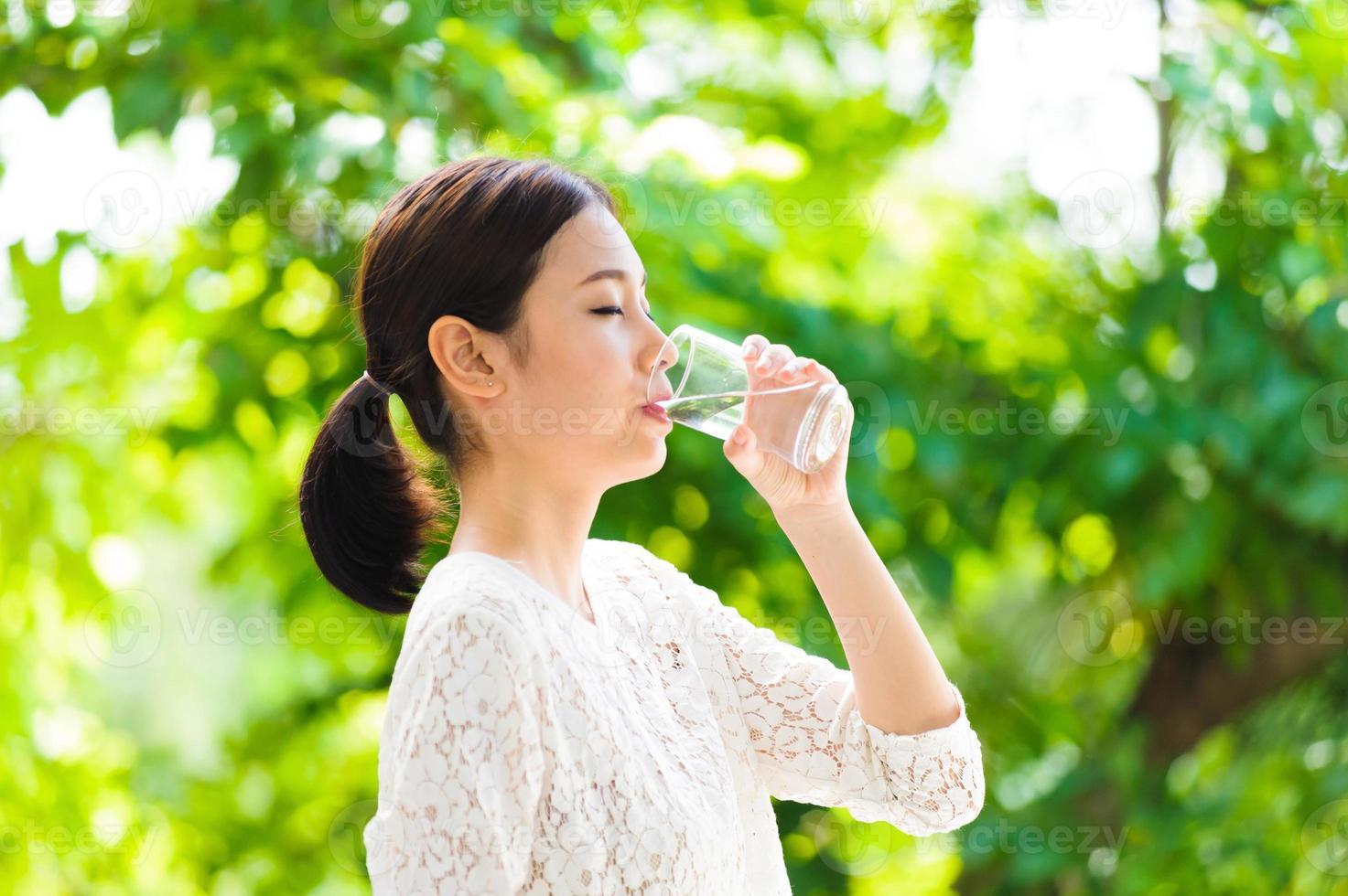 asiatisk ung flicka dricker vatten foto