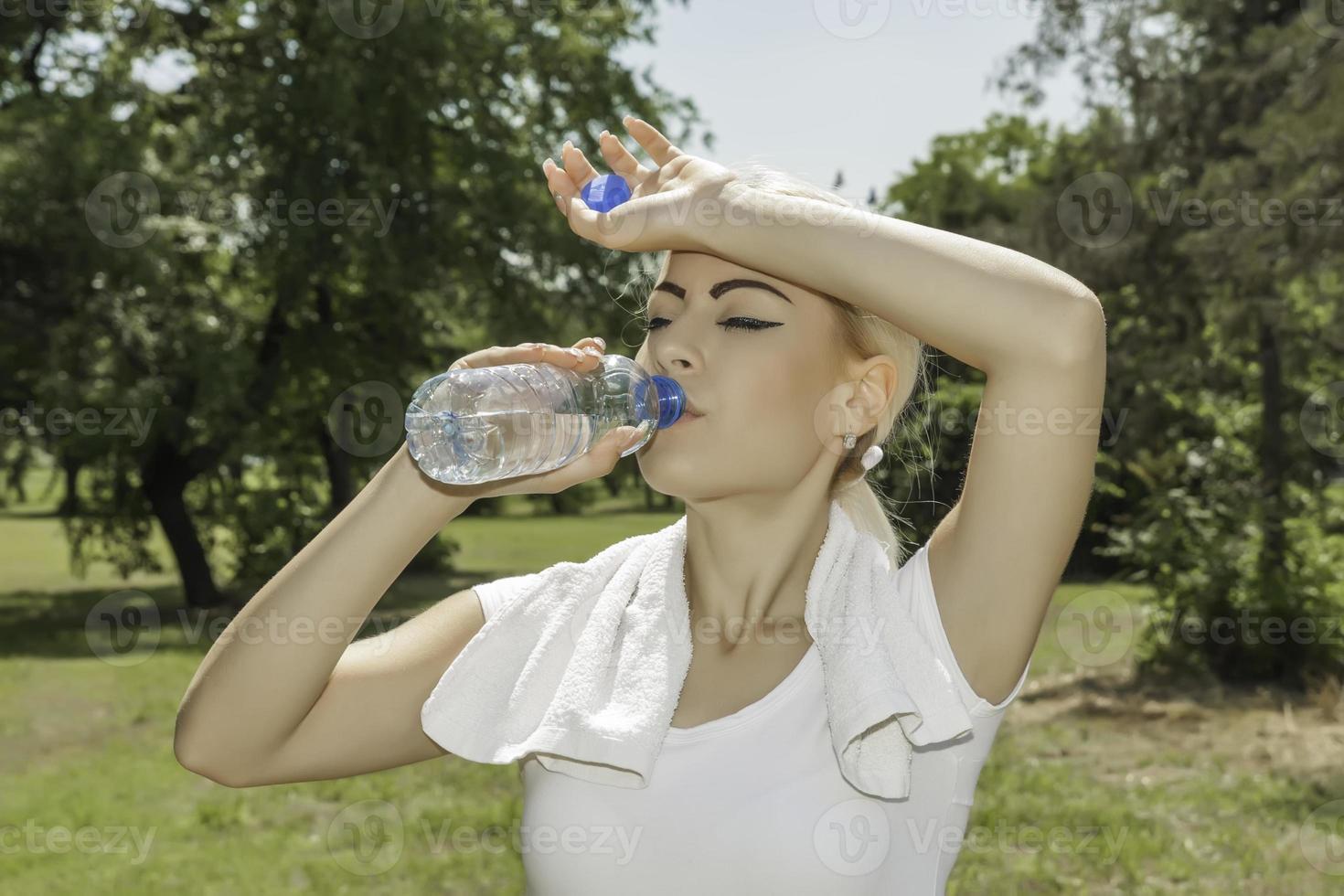 attraktiv blond kvinna dricksvatten foto
