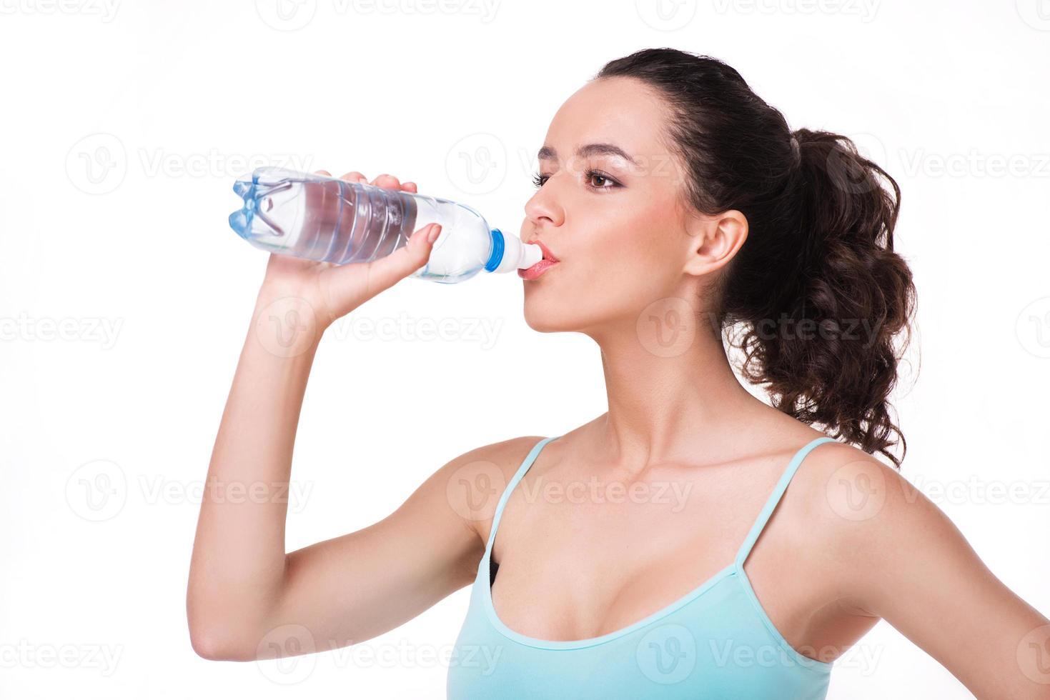 ung sportig kvinna dricksvatten foto