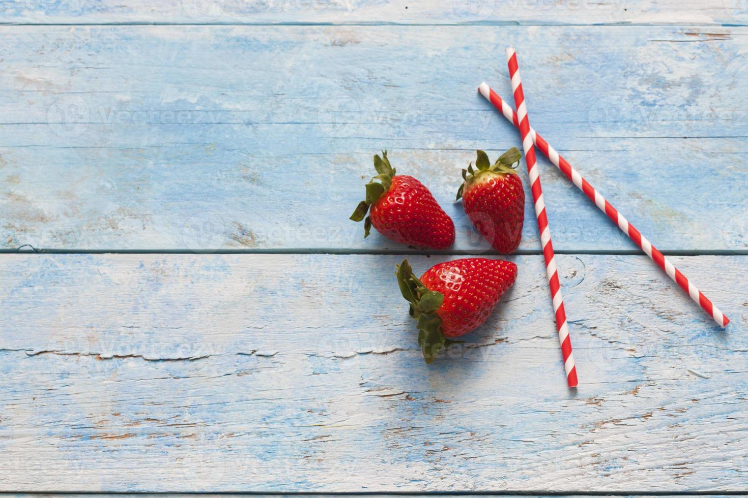 jordgubbar, dricka sugrör, blått trä foto