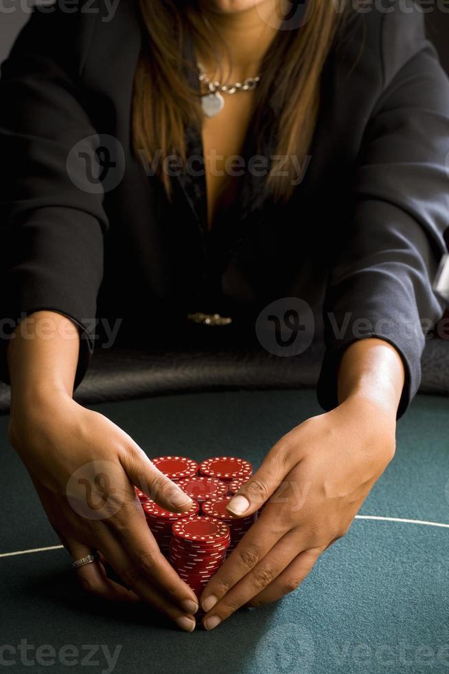 kvinna samlar högar med spelchips på bordet, mitten avsnitt foto
