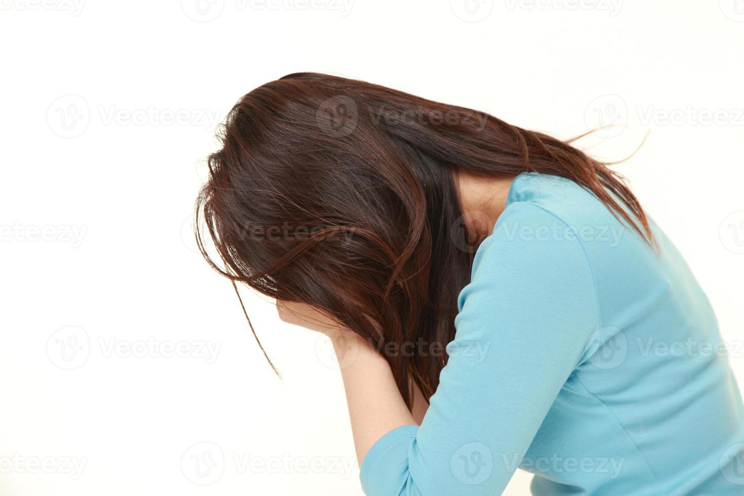 långhårig kvinna i blått med ansiktet begravd på händerna foto