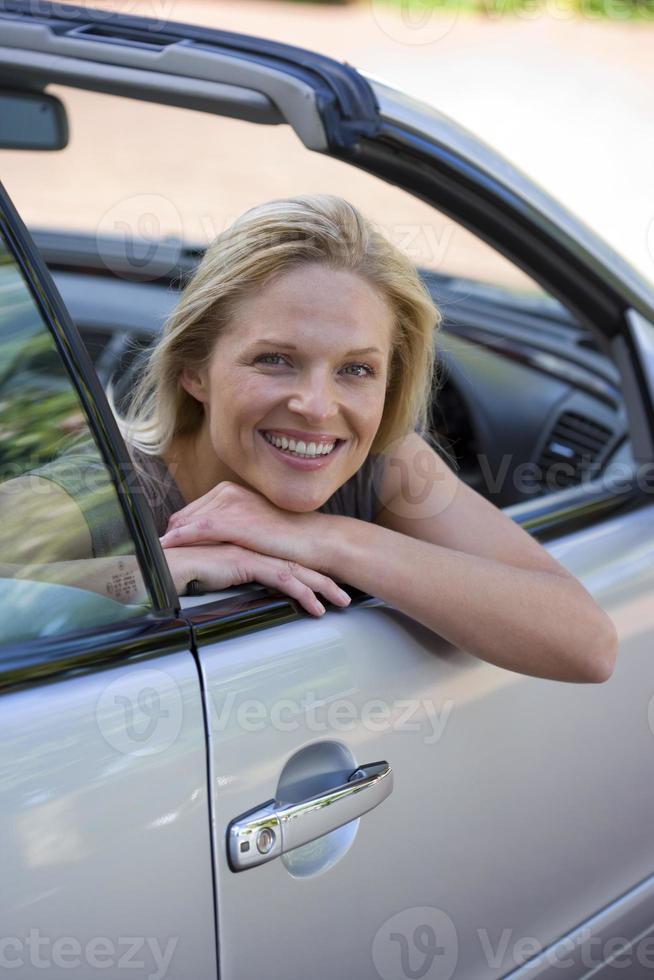 kvinna sitter i körplats på parkerad bil på uppfart foto