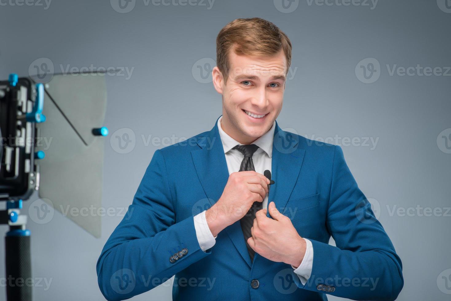 leende nyhetsman som justerar mikrofonen foto