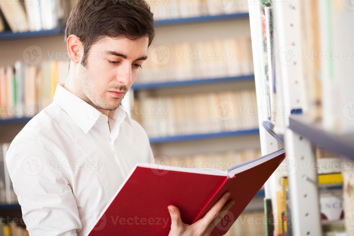 man tar en bok foto
