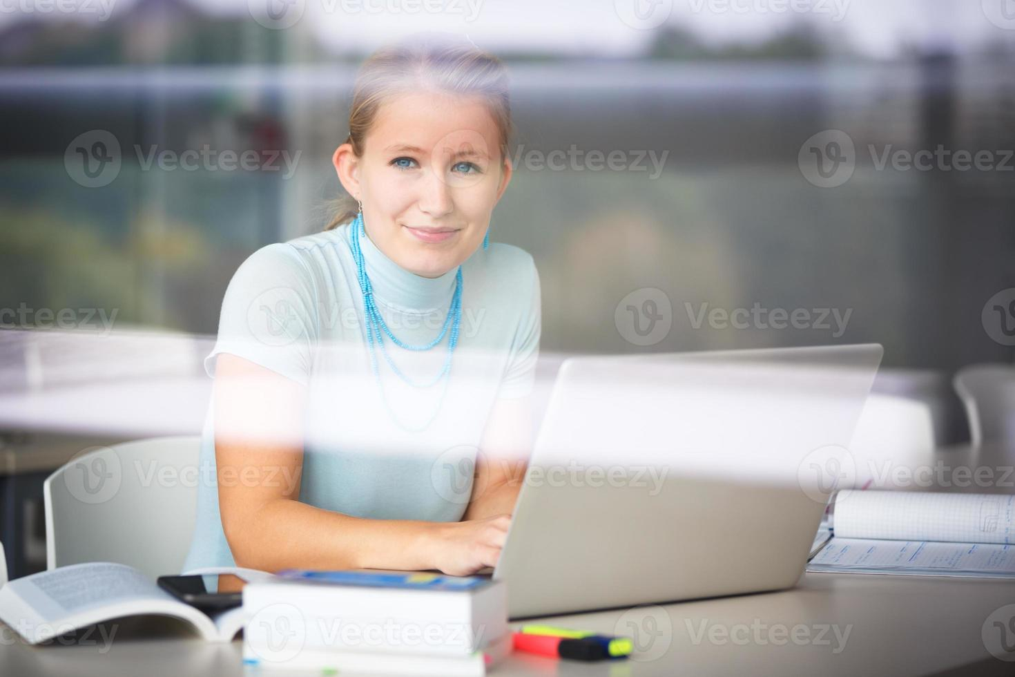 vacker, kvinnlig student i ett gymnasialbibliotek foto