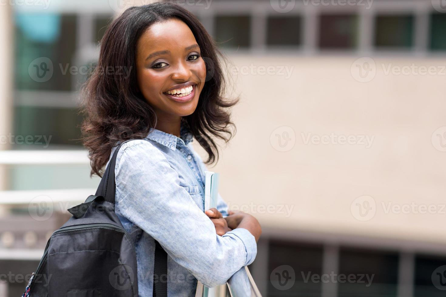 ung afrikansk universitetsstudent som håller böcker foto
