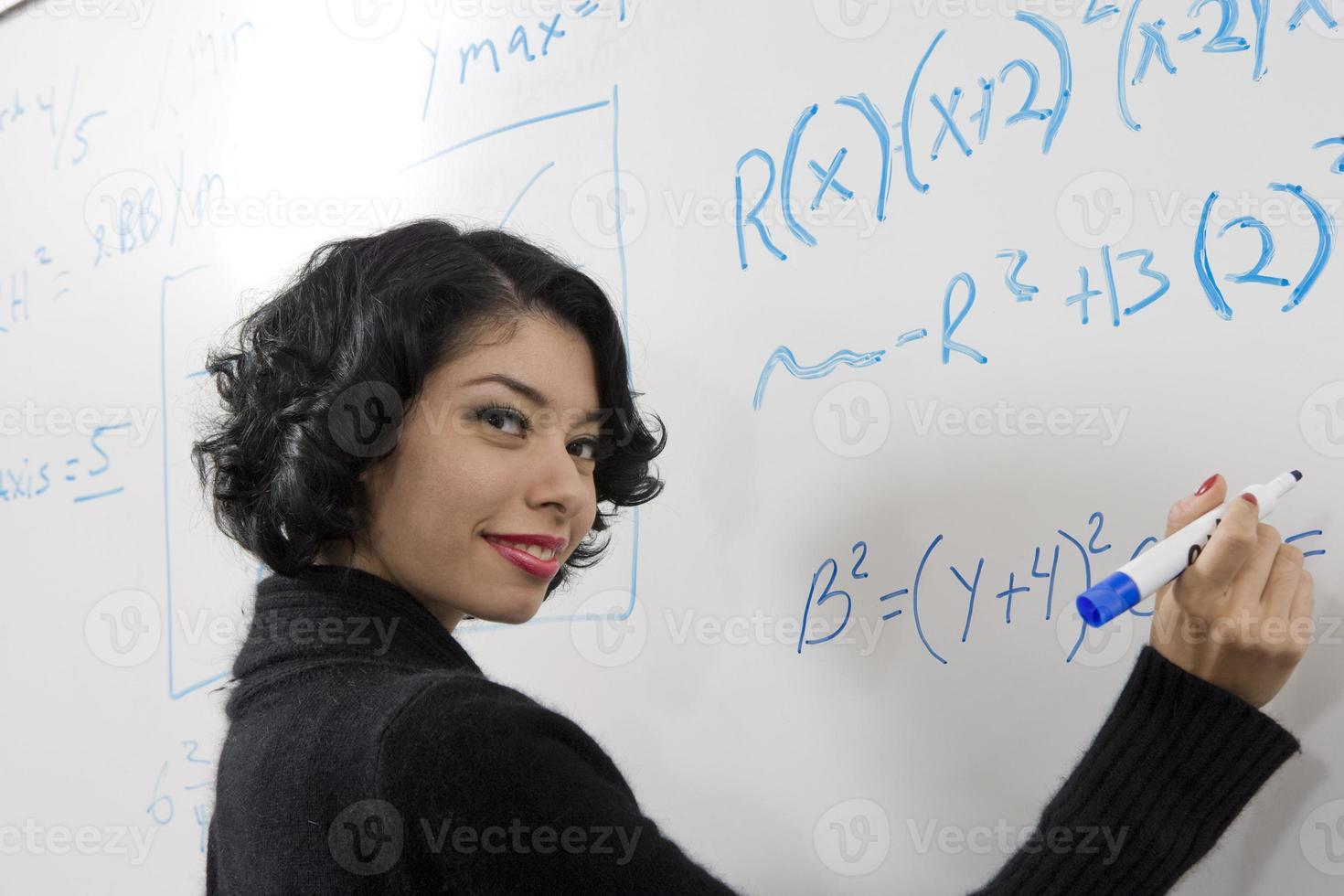 kvinnlig student som skriver matematikekvationer på whiteboard foto