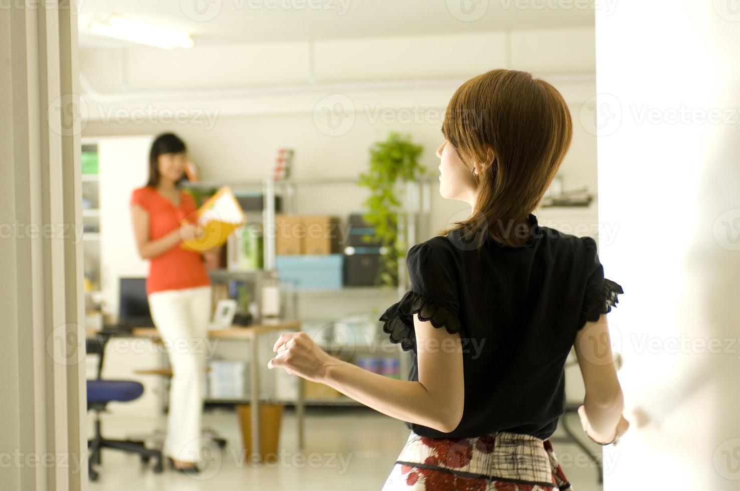 två unga japanska kvinnor som arbetar på kontoret foto