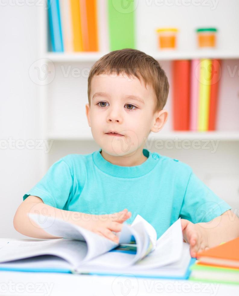 lilla pojken läser en bok foto