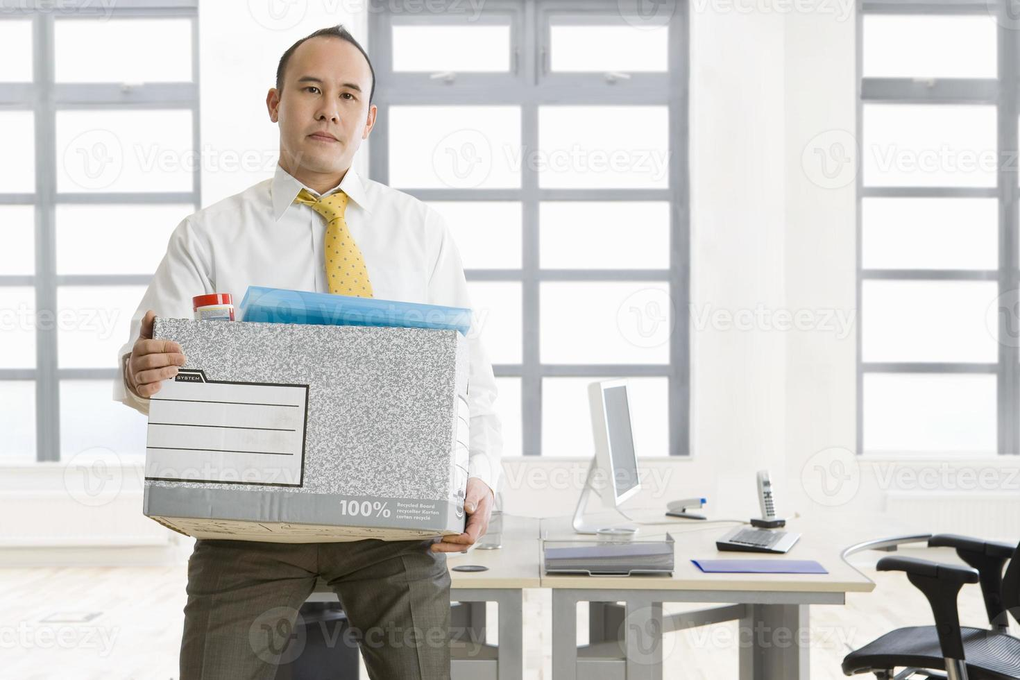 affärsman innehar låda med tillhörigheter i office foto