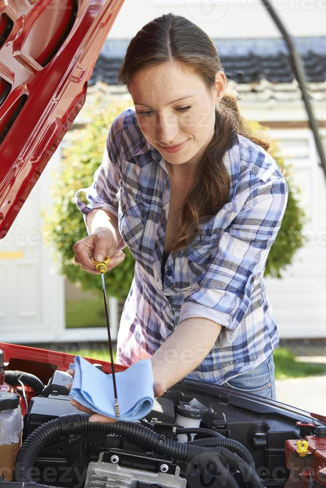 kvinna som kontrollerar bilmotorns oljenivå under huven med mätstift foto