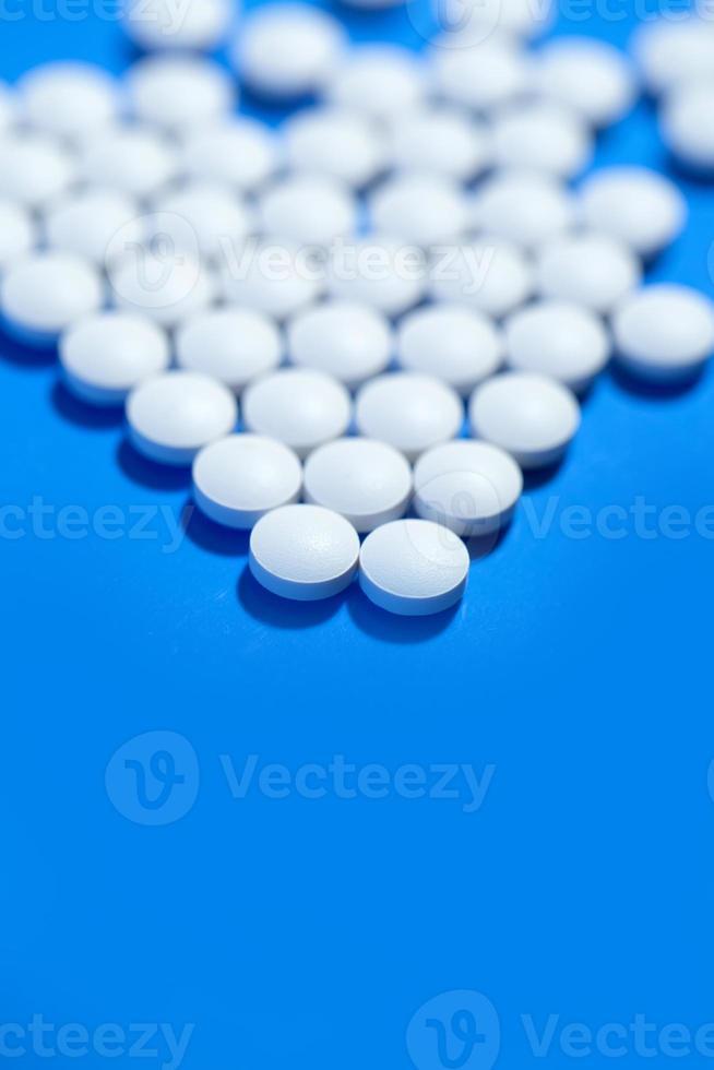 piller. vita medicinska piller på blå bakgrund foto