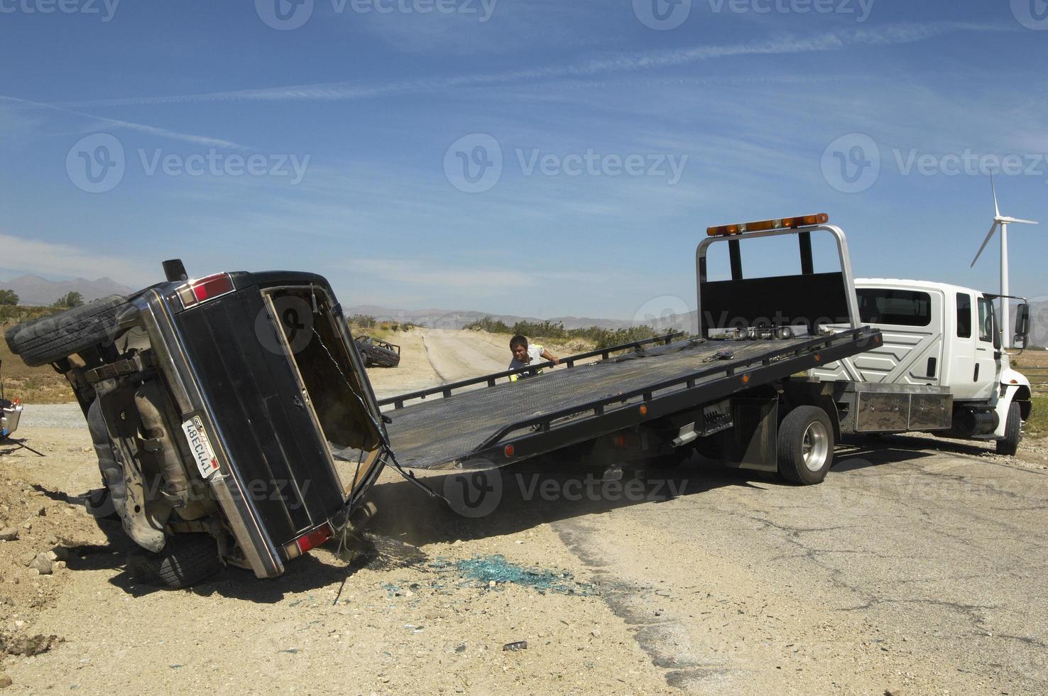 man förbereder sig för att lyfta kraschad bil på dragbilen foto