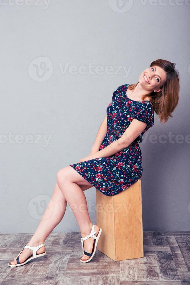 kvinna i klänning som sitter på trälådan foto