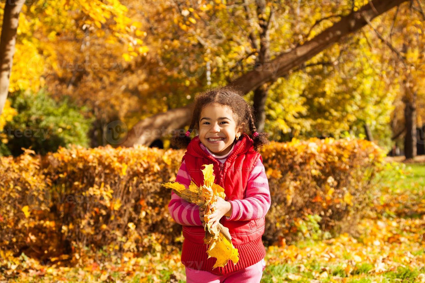 trevlig liten flicka med massa gula blad foto