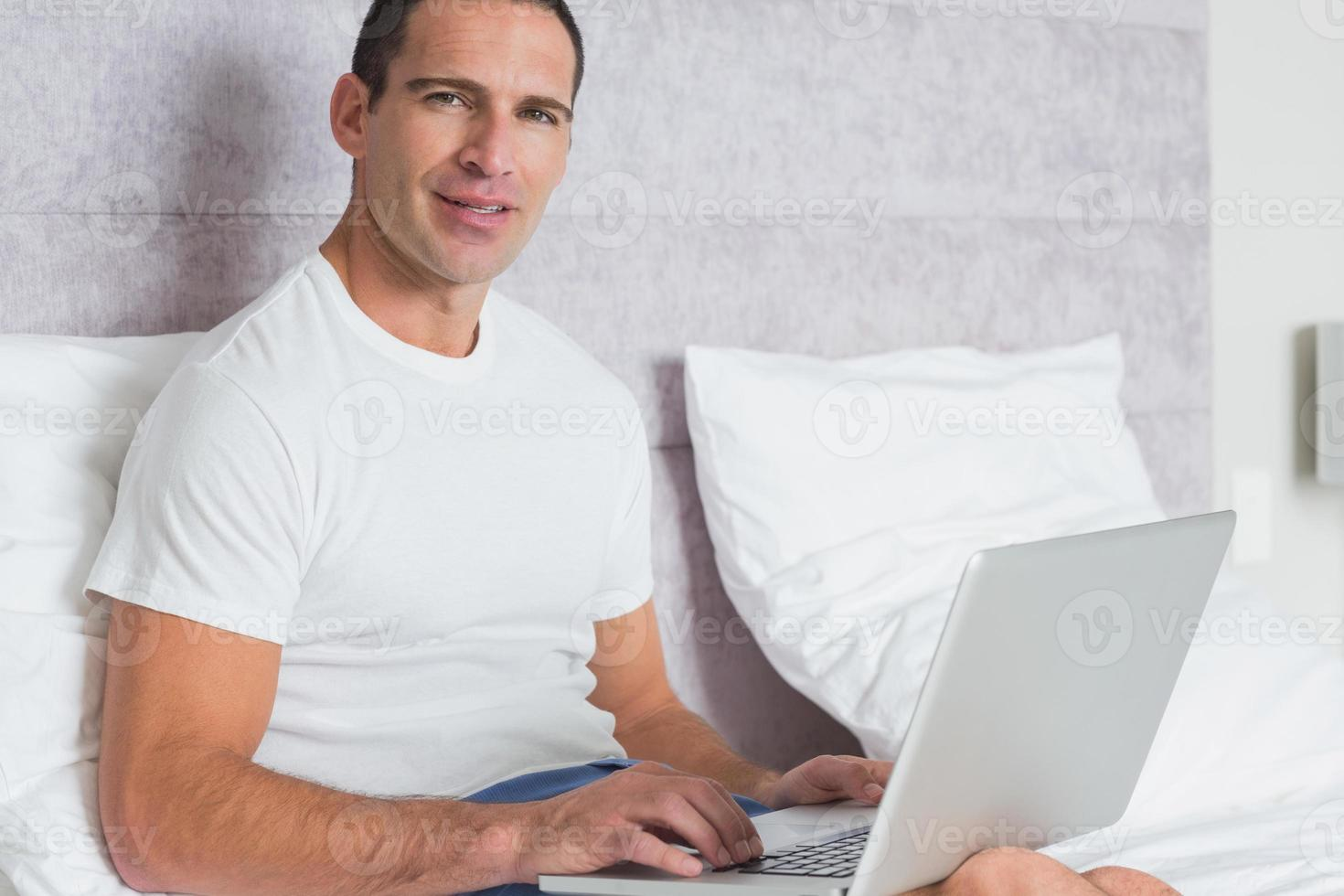 glad man som använder bärbar dator på sängen foto