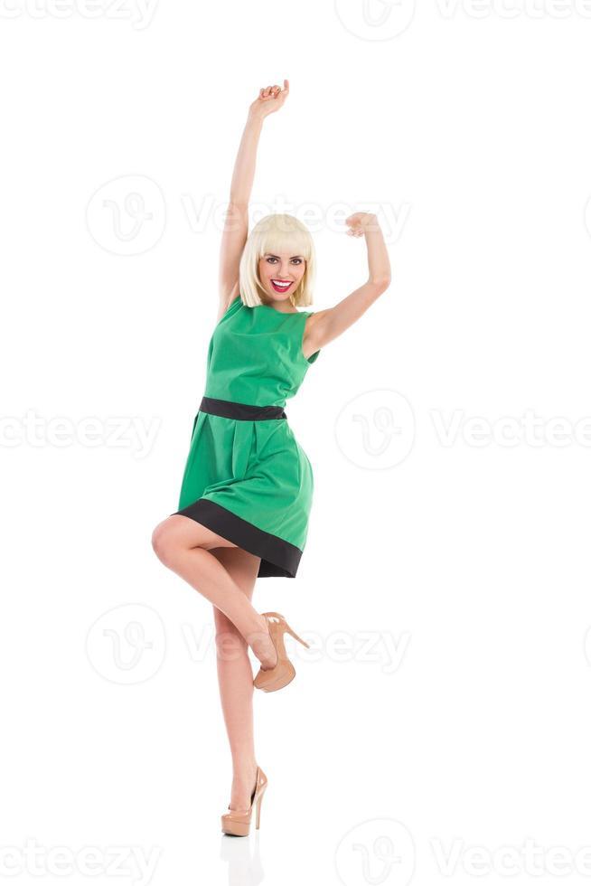 jublande blond tjej i grön klänning foto