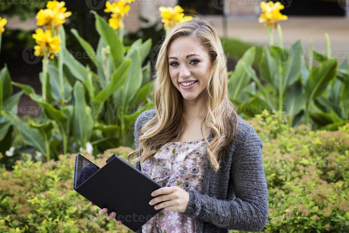 glad vacker högskolestudent använder surfplatta foto
