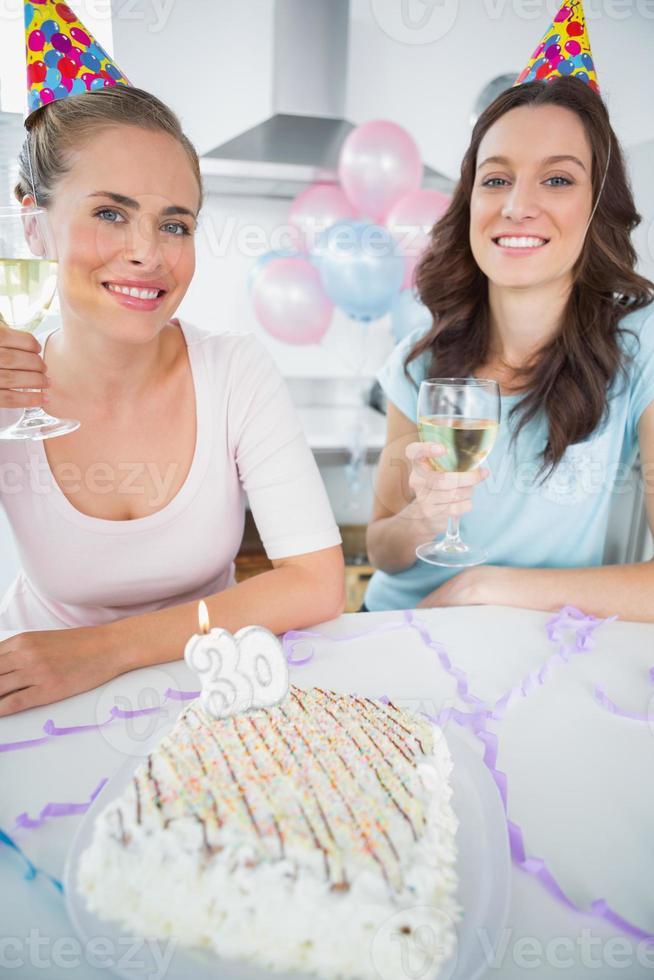 glada kvinnor med vitt vin och födelsedagstårta foto