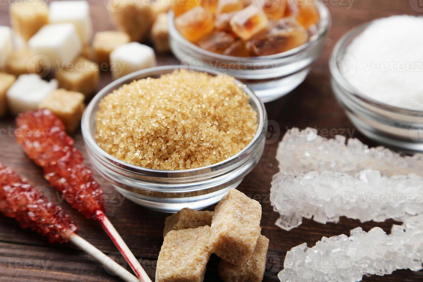 olika sorters socker på brun träbakgrund foto