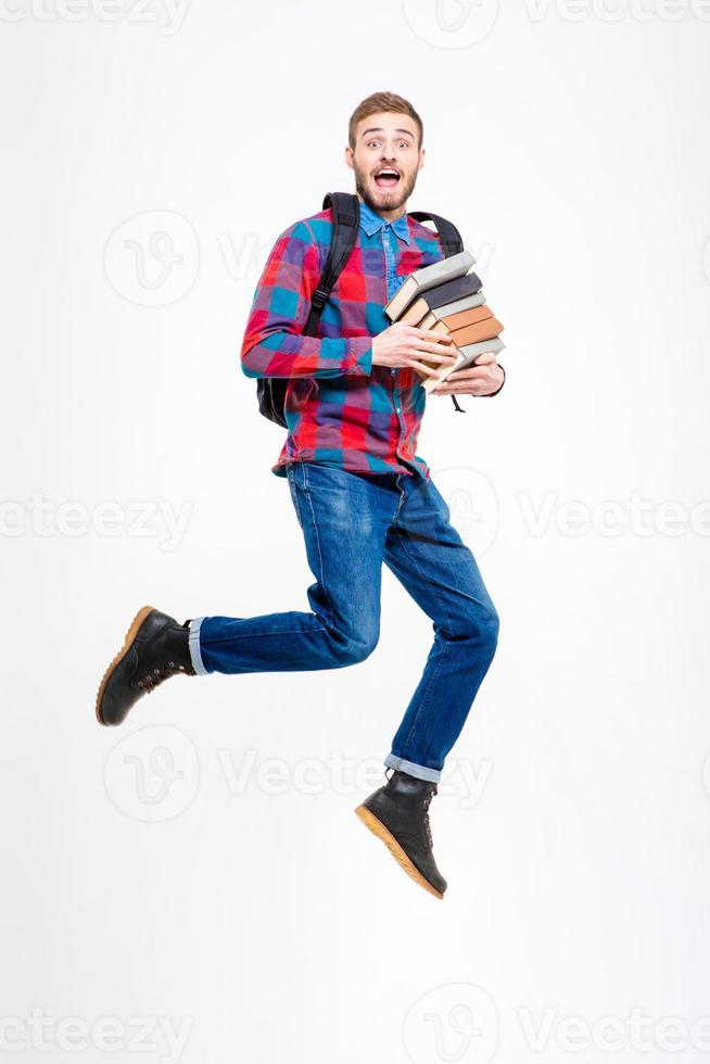 glad glad student med ryggsäck som håller böcker och hoppning foto