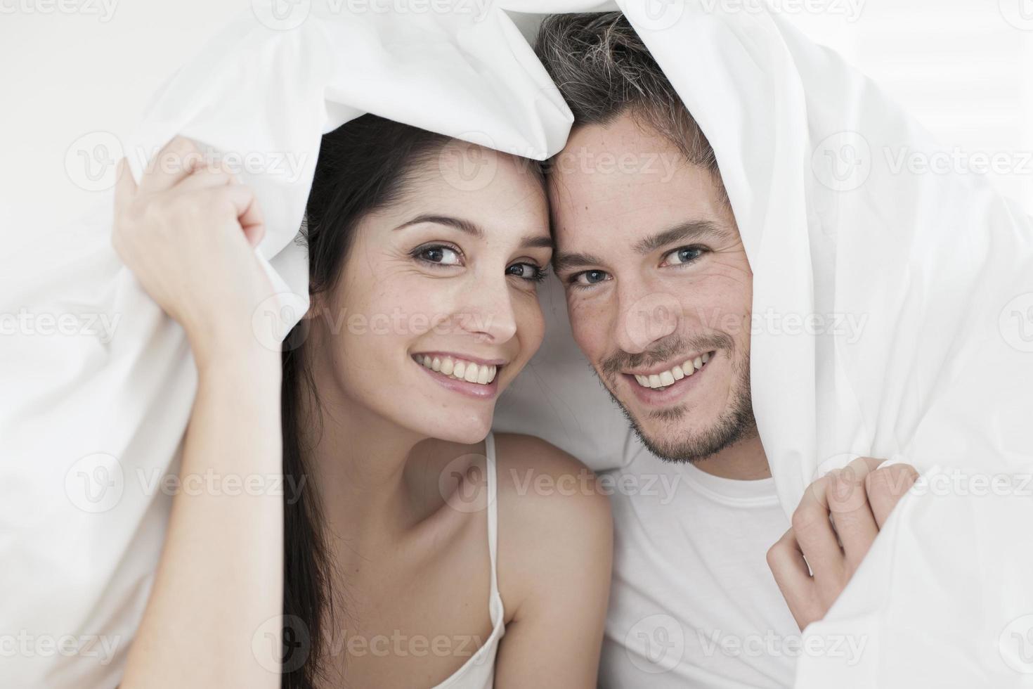 glada unga par lindade i sin täcke foto