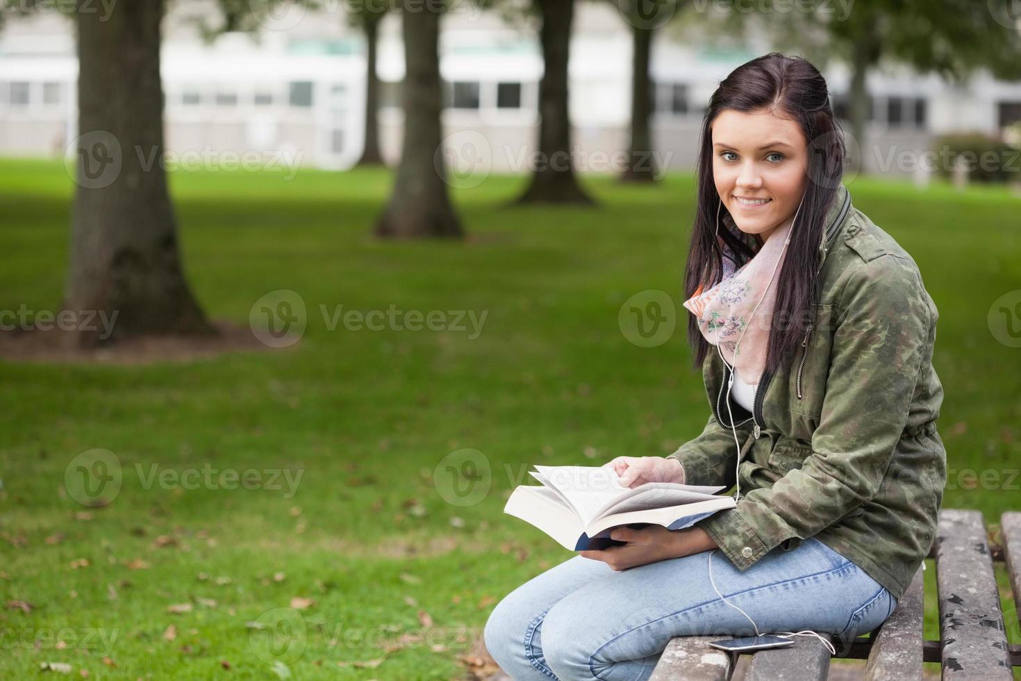 glad brunett student sitter på bänkläsning foto