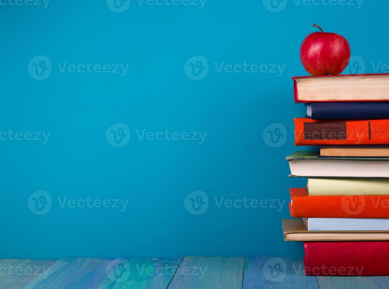 bunt med färgglada böcker, grungy blå bakgrund, fritt kopieringsutrymme foto
