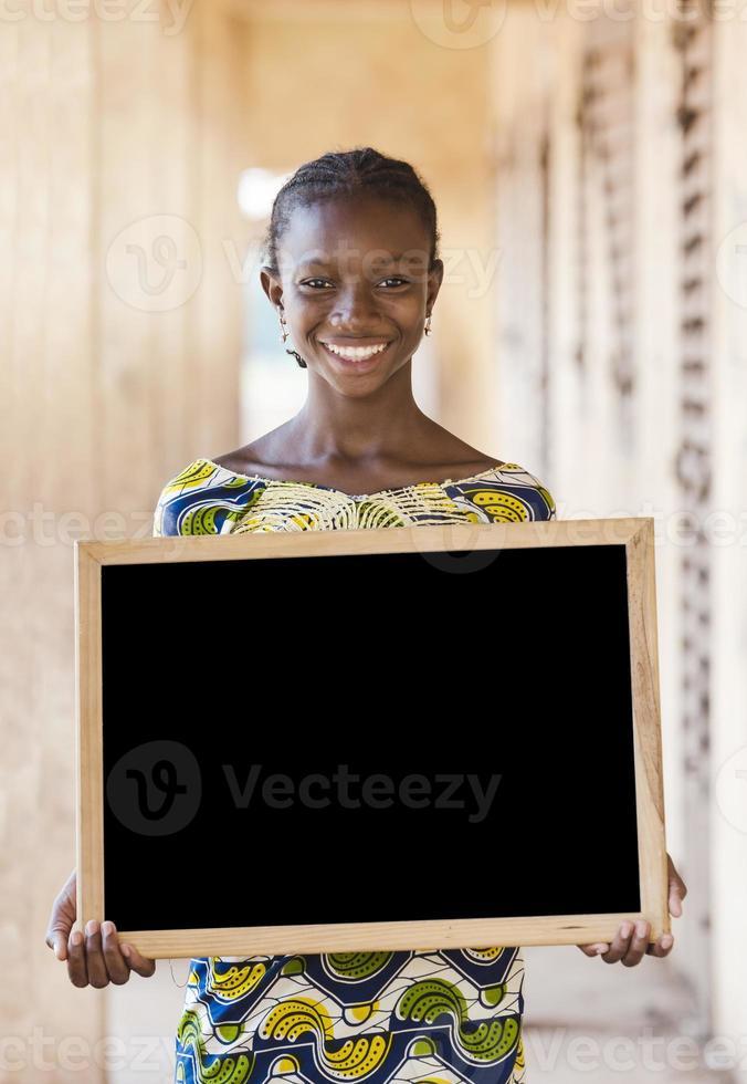 kopieringsutrymme: underbar afrikansk etnicitet tonårsskolflicka som håller tavlan foto