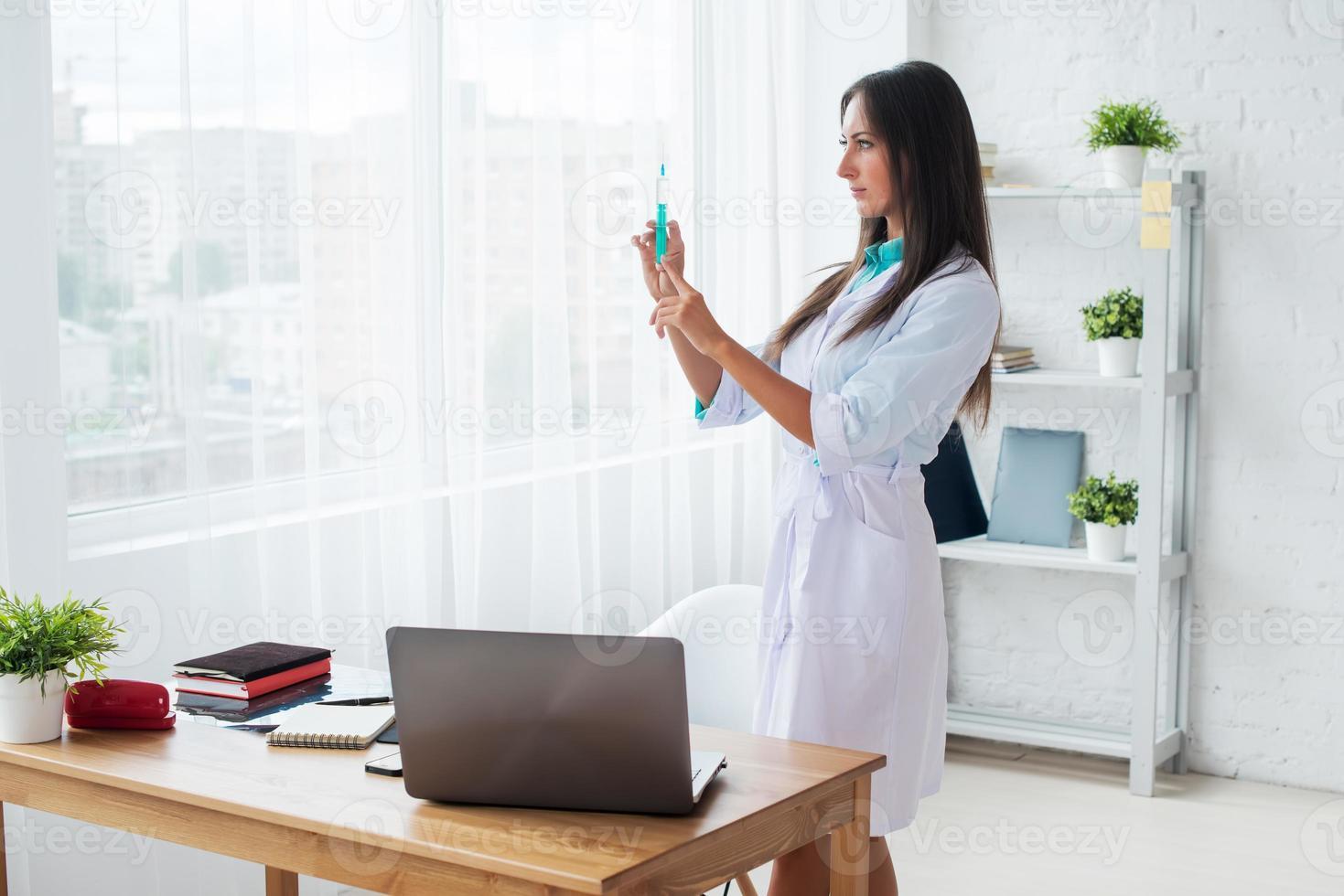 kvinnlig läkare eller sjuksköterska med spruta på sjukhus foto