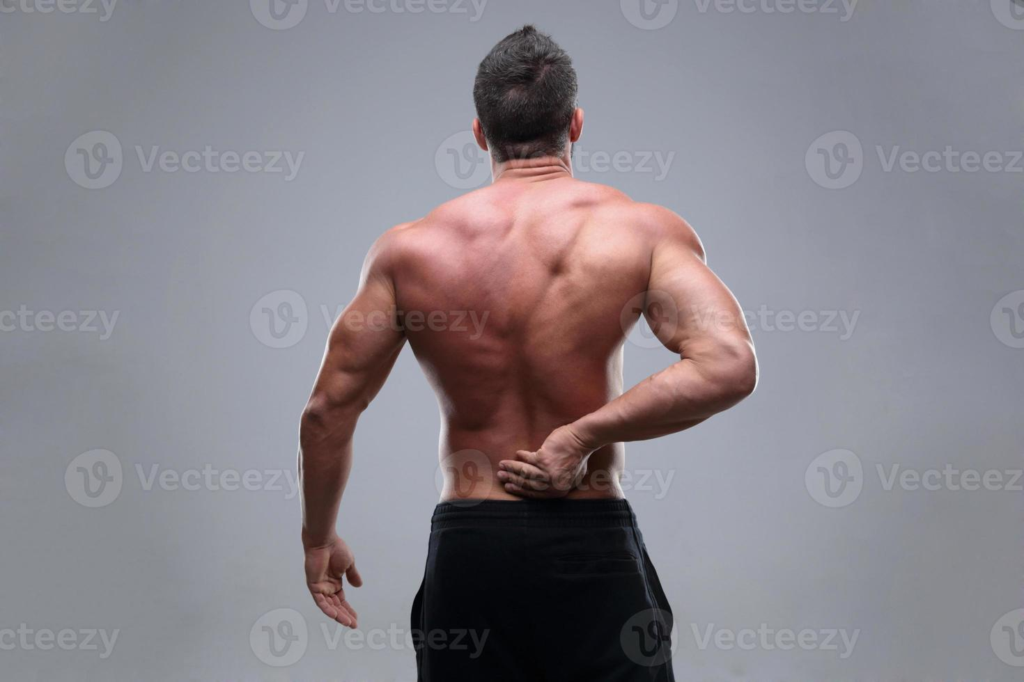 muskulös man med ryggsmärta foto