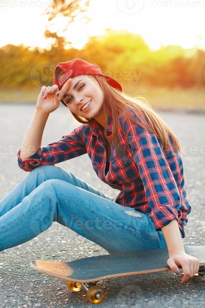 flicka i en skjorta och en baseballmössa vid solnedgången foto
