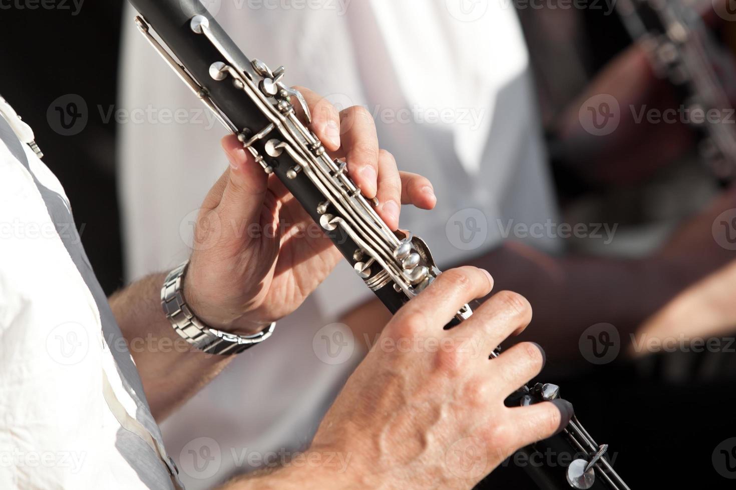mänskliga händer som spelar en klarinett foto