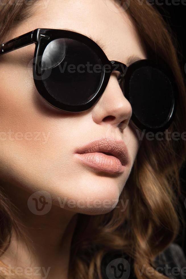 vacker flicka i mörka solglasögon, med lockar och kvällsmakeup. foto