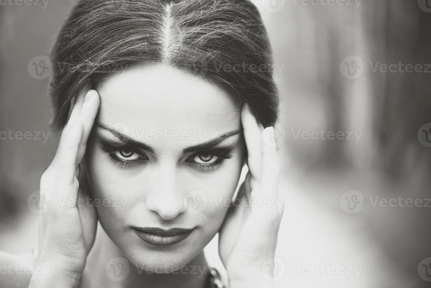söt brunett tjej vidrör hennes huvud eftersom huvudvärk foto