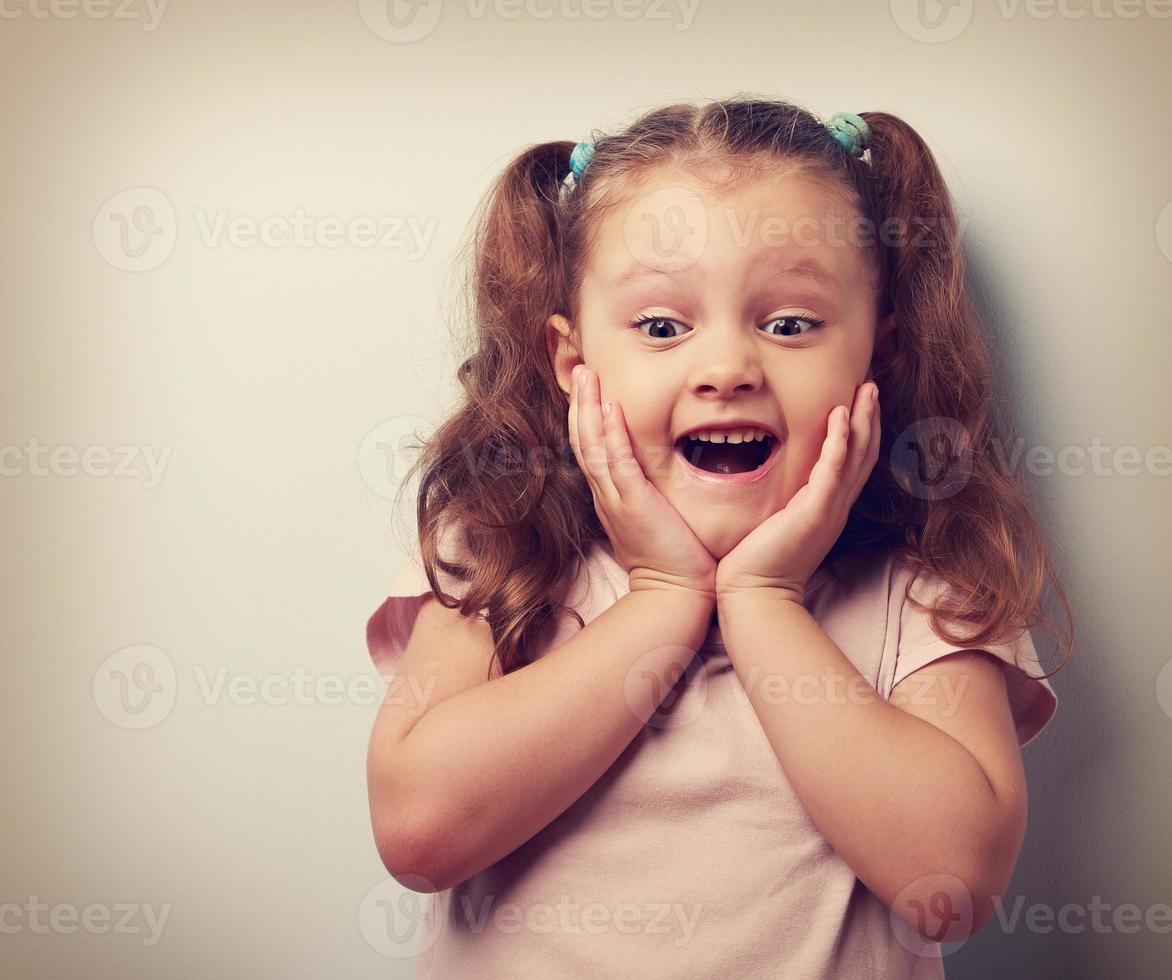 glad mycket upphetsad barnflicka med öppen mun ute. närbild foto