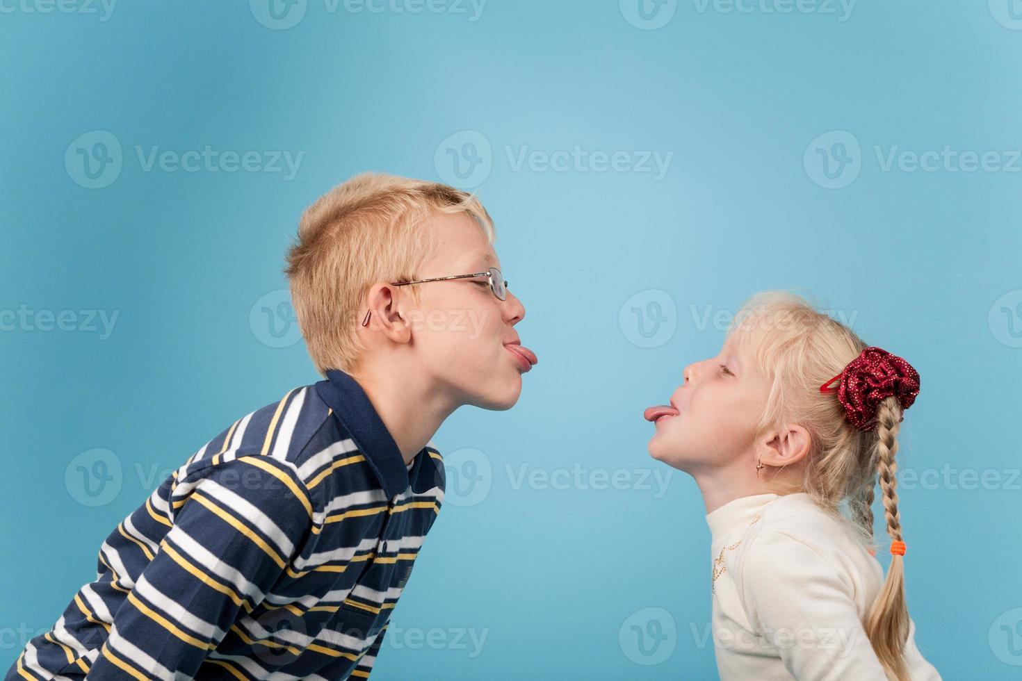 tonårspojke och flicka sticker ut tungor till varandra foto