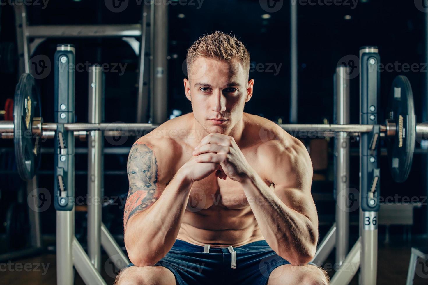närbild porträtt av en muskulös man träning med skivstång på foto