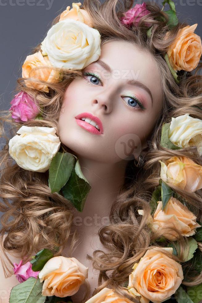 vacker flicka med milt rosa smink och massor av blommor foto