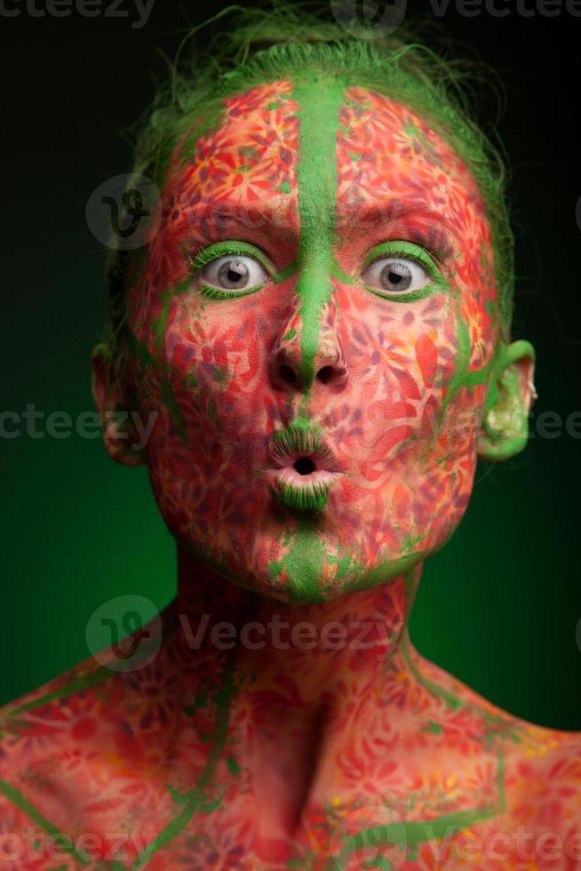 känslomässig kvinna med röda flerlinjer och grönt hår foto